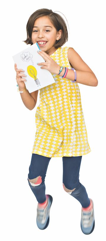 A smiling girl with short brown hair wearing a checkered yellow dress and jeans jumps into the air holding a handmade card.