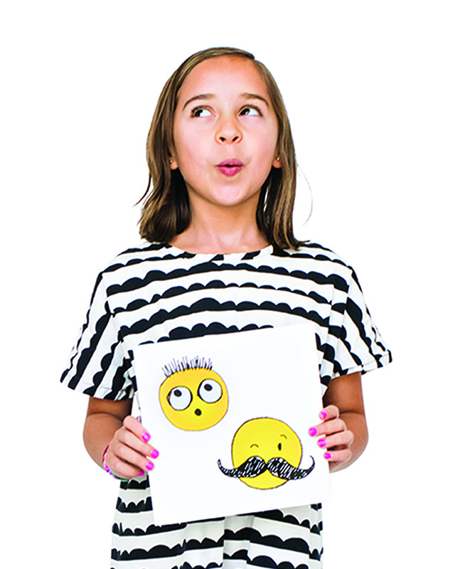"A girl makes a funny face, with her lips scrunched into a small ""O."" She is wearing a black and white striped shirt and showing a drawing of smiley faces."