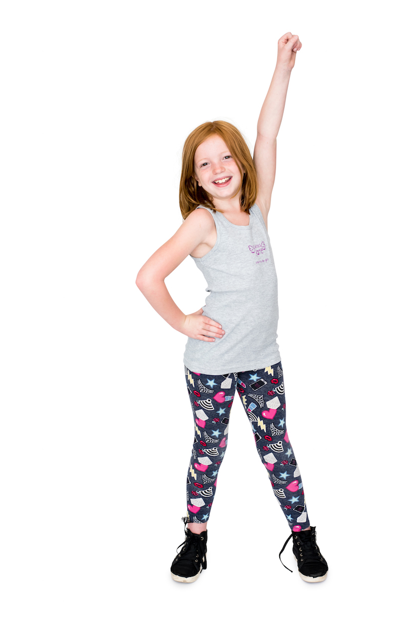 A girl with red hair stands with her feet apart, one hand on her hip and one hand in the air with her fist raised.