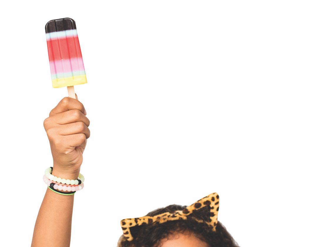 We see the top of a girl's head. She has curly hair and is wearing cat ears, and is holding up colorful soap in the shape of a popsicle.
