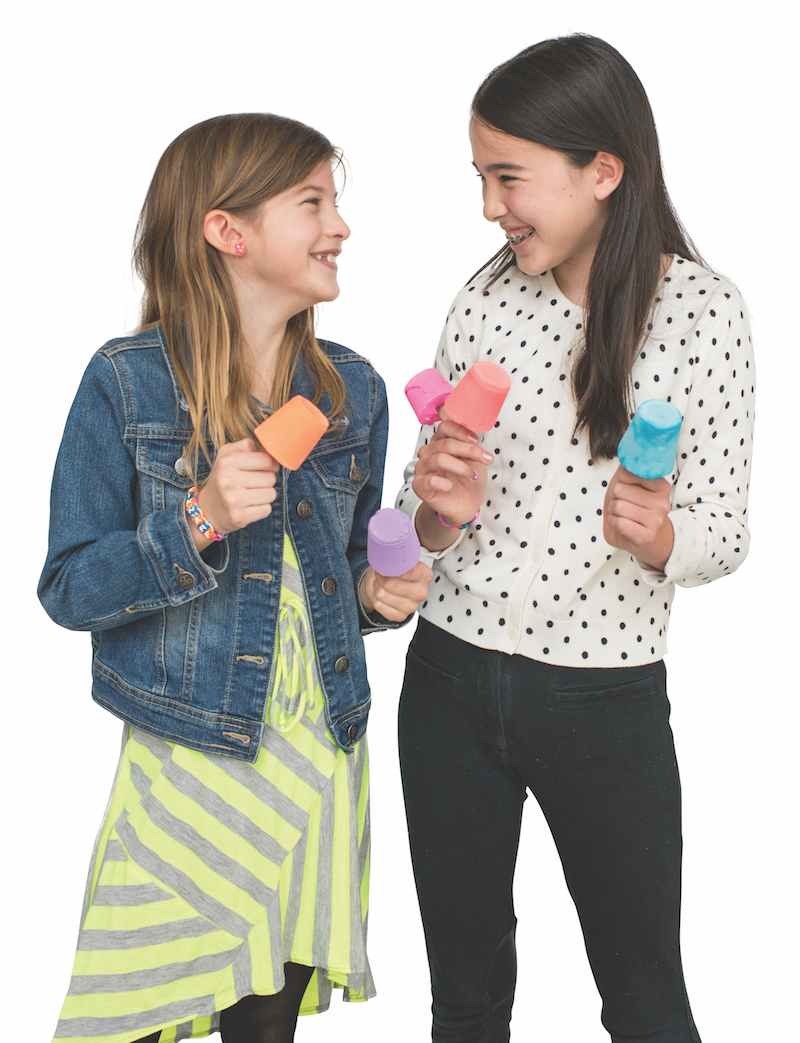 Two smiling young girls hold colorful soaps in the shape of popsicles — soapsicles are projects in Curious Jane Magazine!
