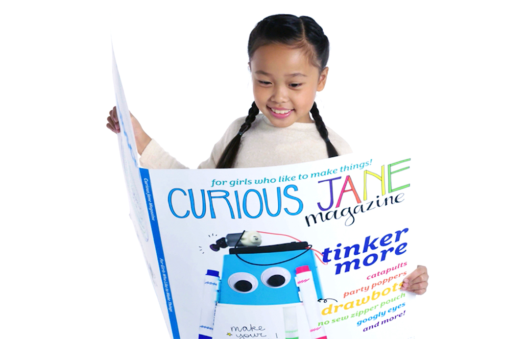 A smiling young girl reads an oversized copy of Curious Jane Magazine.